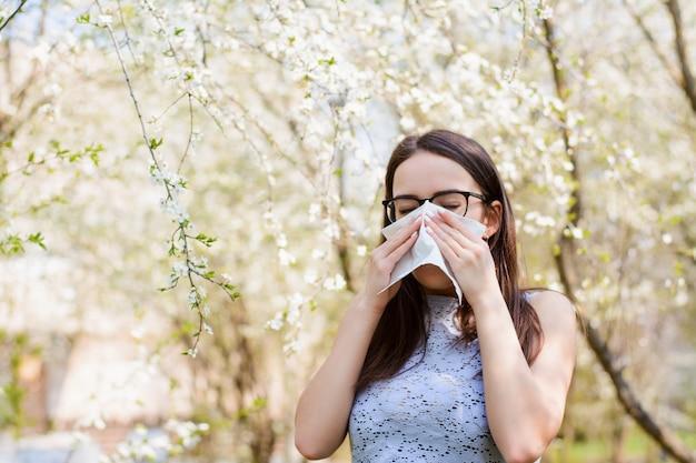 Alergiczna kobieta dmuchająca nosem w kierunku kwitnących drzew