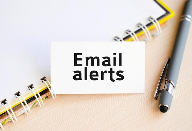 Alerty e-mailowe - tekst na notatniku ze sprężyną i szarą rączką