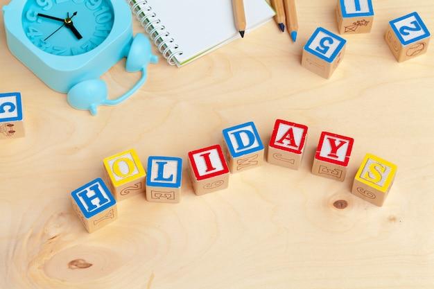 Alfabet blokuje abc na drewnianym stole. tekst - wakacje