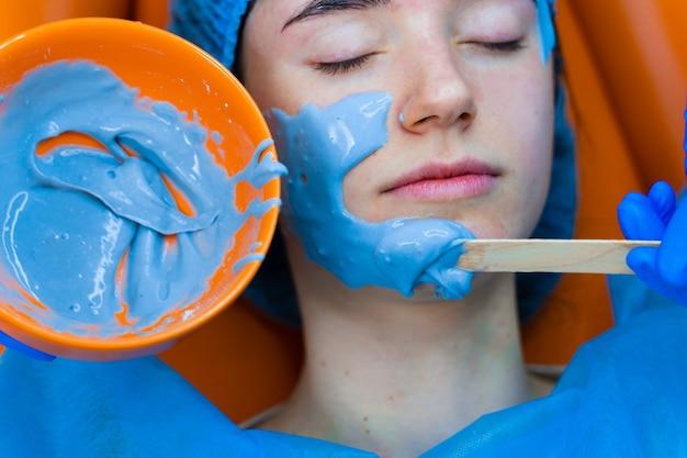 Alginatowa maska nawilżająca do twarzy i skóry młodej dziewczyny. procedura uzdrowiskowa dla odmłodzenia. kosmetyczka rozmazuje niebieską maskę. dermatologia w przychodni lekarskiej