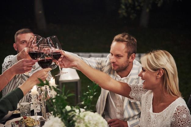 Alkohol daje relaks, więc wypijmy go. przyjaciele spotykają się wieczorem. ładna restauracja na zewnątrz