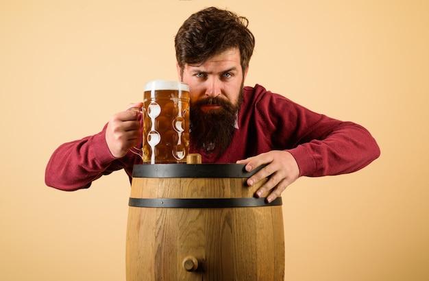 Alkohol piwo drewniana beczka szklanka piwa oktoberfest poważny brodaty mężczyzna ze szklanką piwa spotykamy się