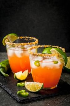Alkohol. tradycyjny meksykański koktajl z ameryki południowej. pikantna michelada z ostrą papryką jalapeno i limonką. na ciemnym kamiennym stole. copyspace
