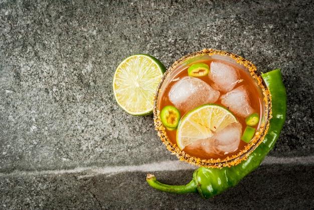 Alkohol. tradycyjny meksykański koktajl z ameryki południowej. pikantna michelada z ostrą papryką jalapeno i limonką. na ciemnym kamiennym stole. widok z góry lato