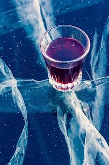 Alkohol w szklance i czysty lód z pięknymi głębokimi pęknięciami. szklanka z czerwoną nalewką stoi na przezroczystym lodzie jeziora. pionowy.