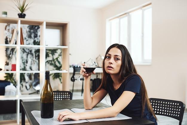 Alkoholizm jest chorobą całej osoby, młodej kobiety pijącej samotnie czerwone wino w