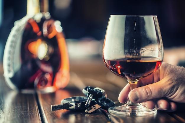 Alkoholizm. puchar koniaku lub brandy ręcznie człowiek kluczyki do samochodu i nieodpowiedzialny kierowca.
