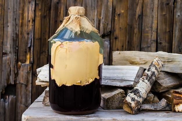 Alkoholowa nalewka brzozowa rzemieślnicza w dużej szklanej butelce na drewnianym stole, rosyjska receptura ludowa.