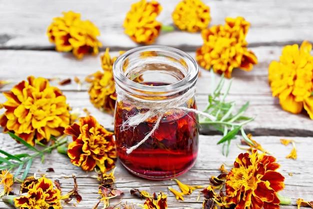 Alkoholowa nalewka z nagietków w szklanym słoju, świeże i suszone kwiaty na tle starej drewnianej deski