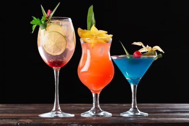 Alkoholowe i bezalkoholowe koktajle na drewnianym stole. letnie zimne napoje