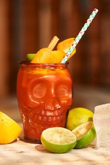 Alkoholowy koktajl mai tai z domowym przyprawionym rumem i syropem migdałowym z sokiem z limonki w szklanej zlewce w kształcie czaszek i cytryny na drewnianym stole