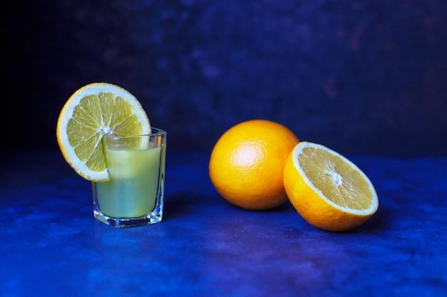 Alkoholowy napój pomarańczowy w kieliszku z plasterkiem pomarańczy i pomarańczy na ciemnym tle
