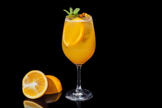 Alkoholowy sok pomarańczowy na czarnym tle ozdobiony plasterkiem pomarańczy i miętą