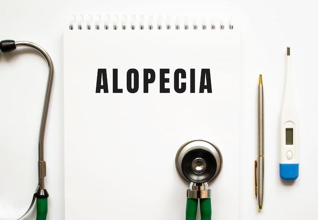 Alopecia tekst zapisany w notatniku leżącym na biurku i stetoskopie. pojęcie medyczne.