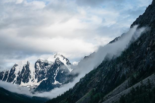 Alpejski krajobraz z dużym lodowcem za górami z lasem pod pochmurnym niebem
