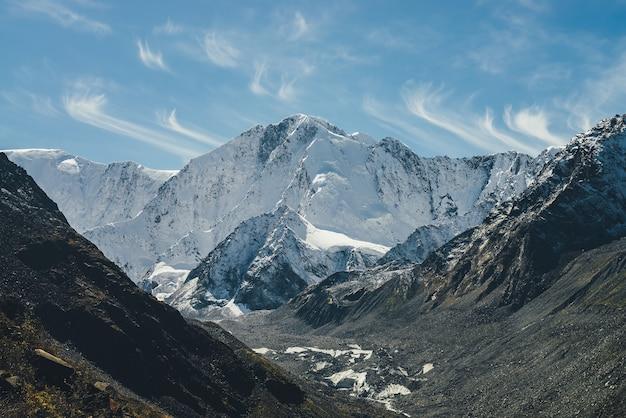 Alpejski słoneczny krajobraz z wysoką śnieżną górą ze szczytem i lodowcem między czarnymi skałami pod chmurami cirrus na niebie. duże pokryte śniegiem góry w promieniach słońca. biały śnieżno-szpiczasty szczyt w słońcu.