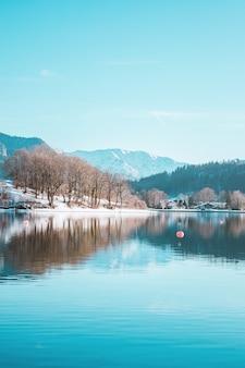 Alpejskie góry i malownicza wioska rybacka na zaśnieżonym wybrzeżu jeziora tegernsee w bawarii