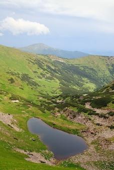 Alpejskie jezioro brebeneckul w letnim wąwozie górskim przed burzą (ukraina, czarnogóra, karpaty)