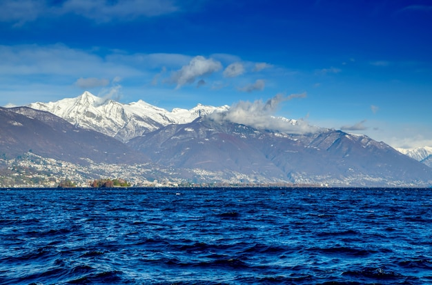 Alpejskie jezioro maggiore z wyspami brissago i ośnieżonymi szczytami w ticino w szwajcarii