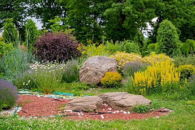 Alpejskie wzgórze z bujną zieloną trawą. trawnik i kręta ścieżka w pięknym ogrodzie w stylu angielskim.