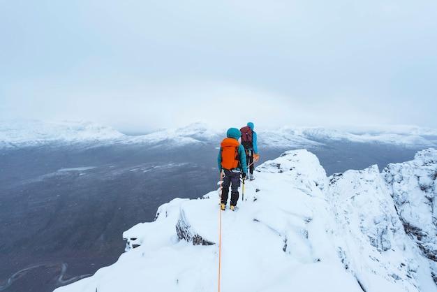 Alpiniści wspinający się na ośnieżony grzbiet liathach w szkocji