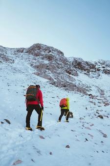 Alpiniści wspinający się na zaśnieżoną górę