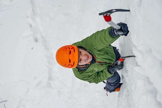 Alpinista człowiek z lodowymi narzędziami topór w pomarańczowym hełmie, wspinaczka na dużą ścianę lodu. portret sportowy na świeżym powietrzu