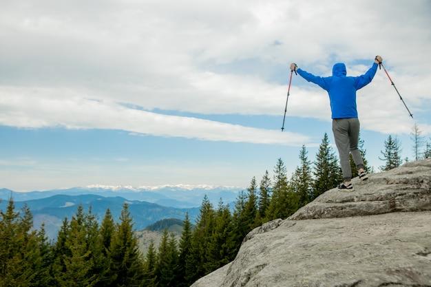 Alpinista jest wysoko w górach na tle nieba, świętuje zwycięstwo, podnosząc ręce do góry.
