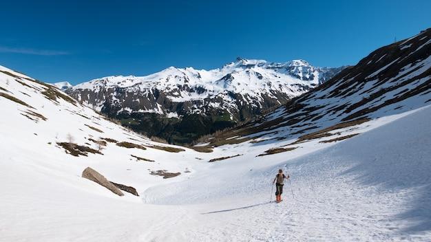 Alpinista piesze wycieczki narciarskie na zaśnieżonym zboczu w kierunku szczytu górskiego. koncepcja pokonania przeciwności losu i osiągnięcia celu.