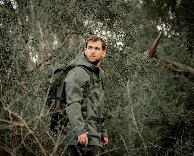 Alpinista ubrany w ciemnozielony w zaroślach