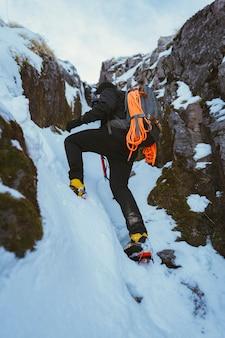 Alpinista wspina się na śnieżną górę
