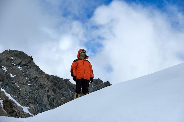 Alpinista wspinacz stoi na szczycie góry. snowy szczyty i niebo, ałtaj, belukha