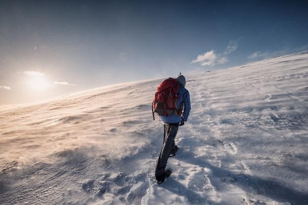 Alpinista wspinaczka na szczyt w zimie