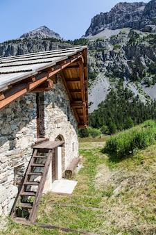 Alpy szwajcarskie, domek górski z kamienia i drewna, sezon letni