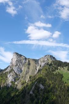 Alpy szwajcarskie porośnięte lasami pod błękitnym pochmurnym niebem w pobliżu granicy z francją
