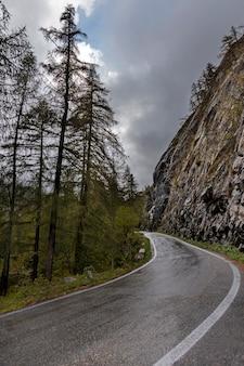 Alpy, włochy. górska droga w pochmurny dzień na jesieni