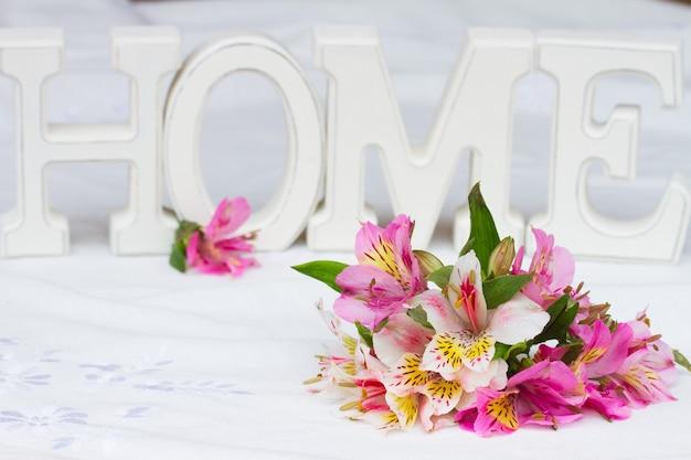 Alstroemeria kwiaty na stole z lnianym obrusem ze znakiem domu w tle