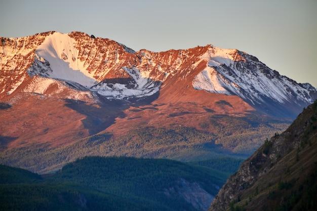 Ałtaj, ośnieżone góry o zachodzie słońca. wieczorne słońce świeci