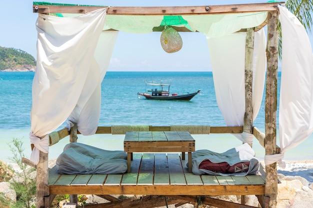 Altana do relaksu z białymi zasłonami na tropikalnej, piaszczystej plaży w pobliżu błękitnej wody morskiej na wyspie koh phangan, tajlandia