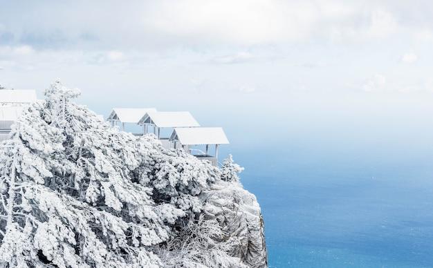 Altana do wypoczynku w zaśnieżonym lesie w górach. pejzaż morski.