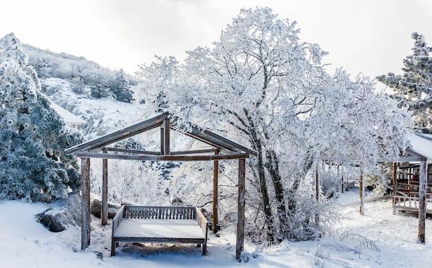 Altana do wypoczynku w zaśnieżonym lesie w górach.