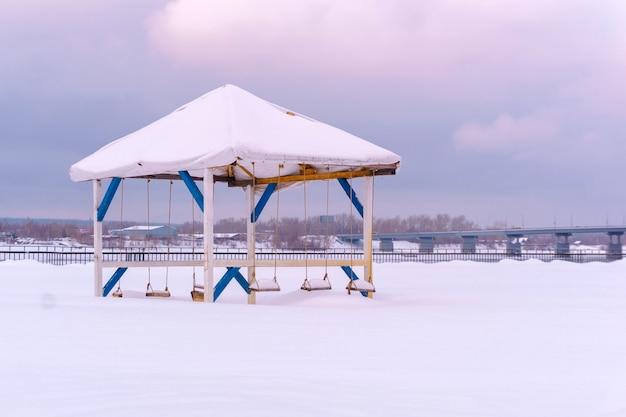 Altana porzucona na zimę z huśtawnymi ławkami wśród zasp na brzegu rzeki