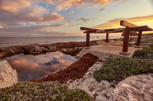 Altana z dwoma hamakami poniżej, naturalnym basenem i zachodem słońca: obraz, który inspiruje do czystego relaksu. widok na prywatne wybrzeże puerto aventuras w meksyku.