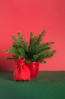 Alternatywna kreatywna choinka w doniczce i worek mikołaja na stół biurowy na czerwono-zielonej przestrzeni