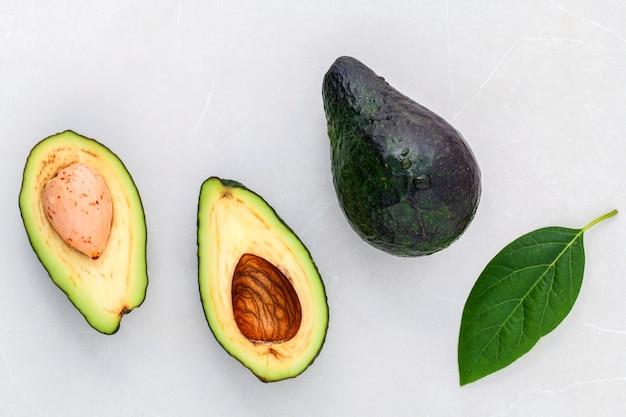 Alternatywna opieka zdrowotna świeży avocado i liście na marmurowym tle.
