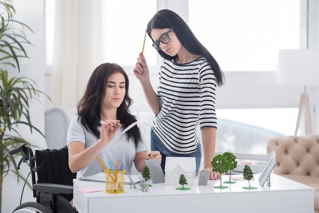 Alternatywne podejście. atrakcyjna koleżanka stojąca i kaleka kobieta niosąca model wiatraka
