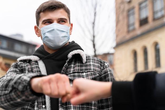 Alternatywne pozdrowienia niemal dotykające pięści uderzają mężczyznę w maskę