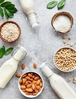 Alternatywne rodzaje mlek wegańskich w szklanych butelkach na betonowym tle. widok z góry