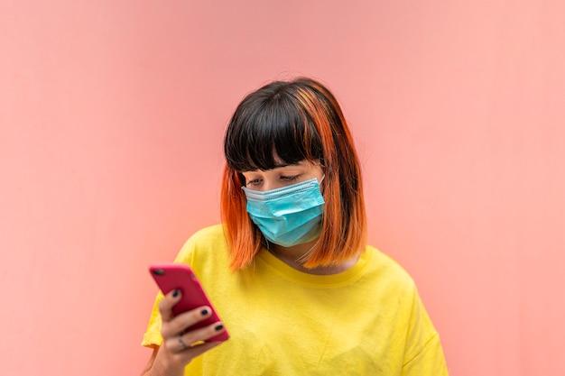 Alternatywny kaukaski model z pomarańczowymi włosami, patrząc na telefon komórkowy w masce ochronnej