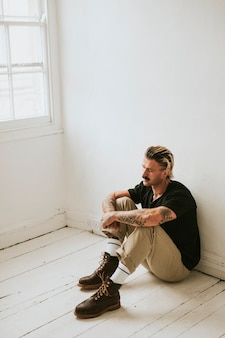Alternatywny mężczyzna siedzący na białej drewnianej podłodze